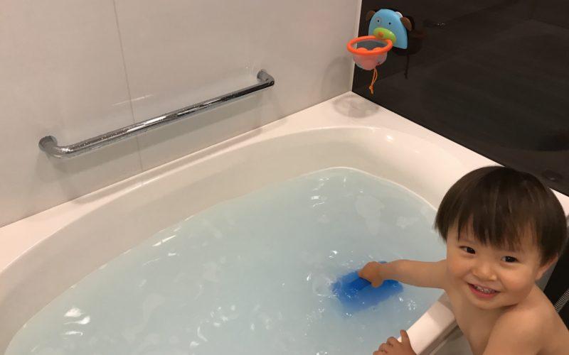 お風呂から湯おけでお湯をすくう1歳児