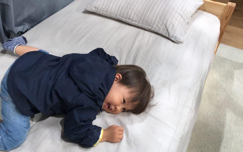 シングルベッドの上に寝転がる1歳児