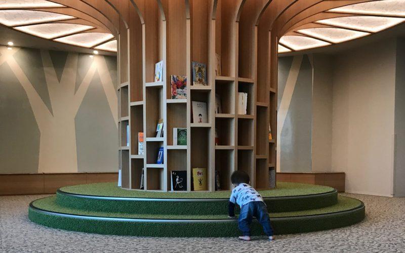 キッズルームの本棚から本を取ろうとする1歳児