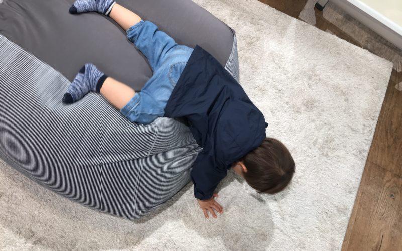 ビーズクッションからじゅうたんの上におりようとしている1歳児