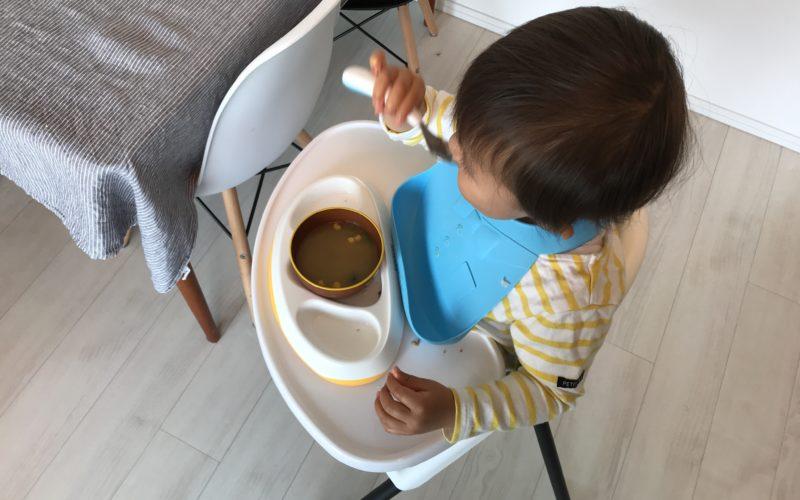 幼児用の食器とカトラリーで昼食を食べる1歳児