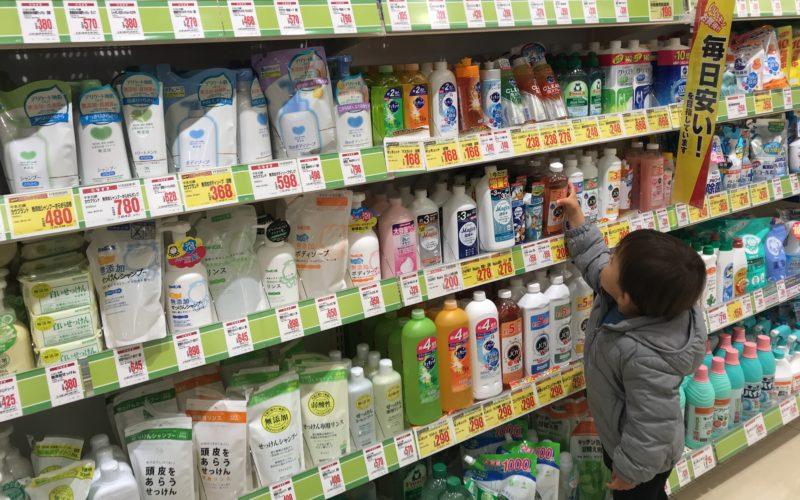 ドラッグストアの店内で商品を手にとる1歳児