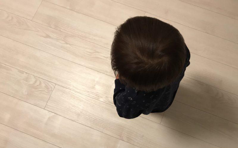 フローリングの上に立つ1歳児