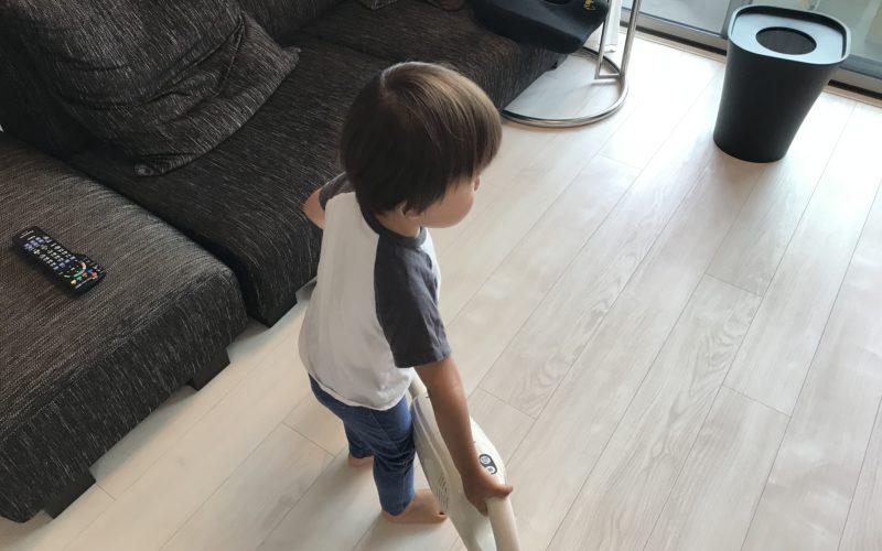 フローリングに掃除機をかける1歳児