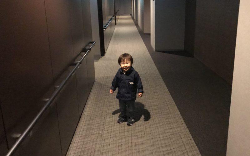 マンションの内廊下を新居の近所への引越し挨拶に向かう1歳児