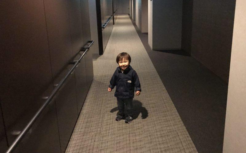マンションの内廊下を新居の近所への引っ越し挨拶に向かう1歳児