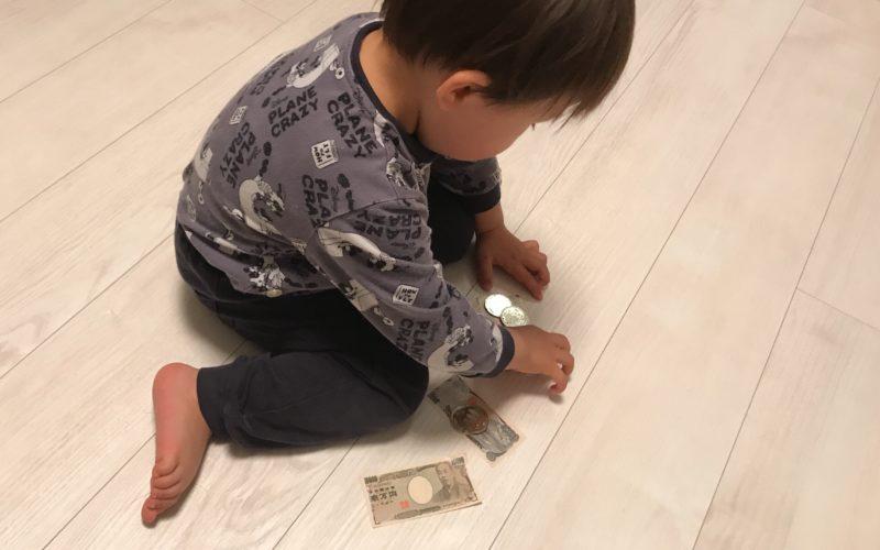 床の上のこども銀行のおかねを拾う1歳児