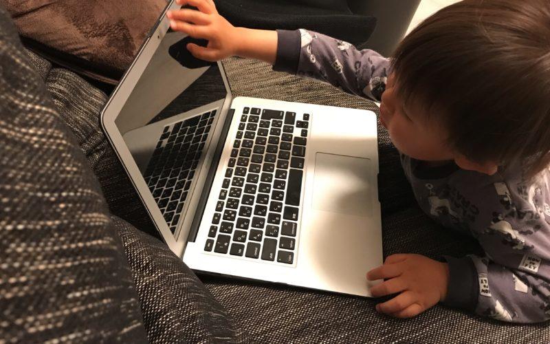 ソファの上のパソコンを操作する1歳児