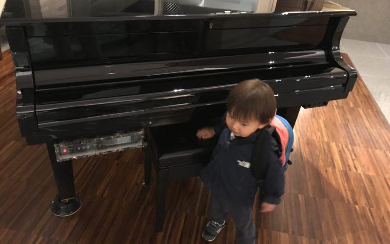 自動演奏のグランドピアノと1歳児
