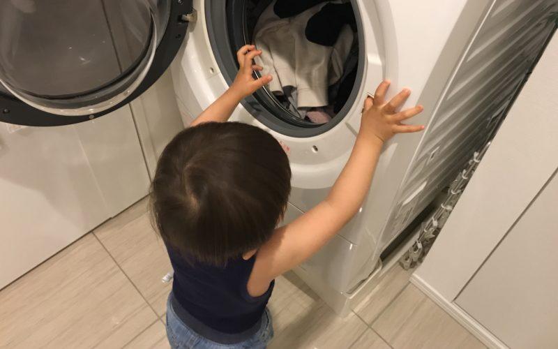 ドラム式洗濯機に洗濯物を入れる1歳児