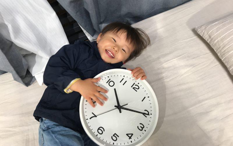 ベッドの上で壁掛け時計をかかえる1歳児