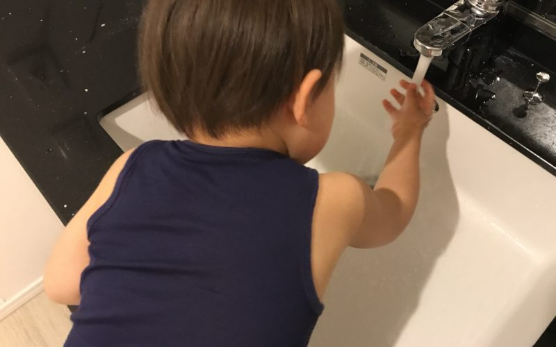 洗面所の水道で手を洗う1歳児