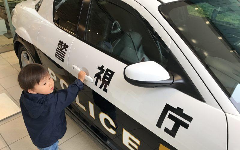 ポリスミュージアムのパトカーに乗り込もうとする1歳児