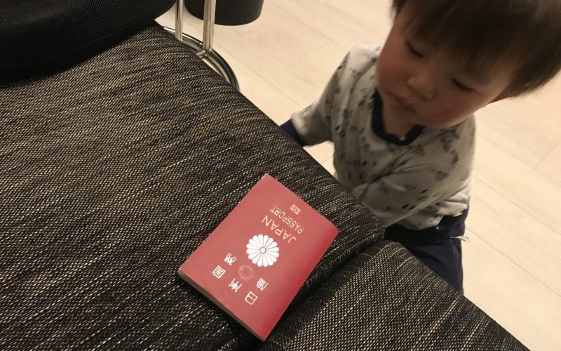 ソファの上のパスポートを見つめる1歳児