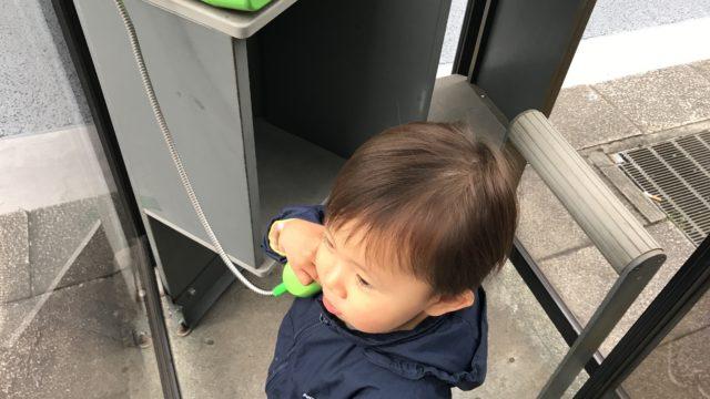電話ボックスで電話をかける1歳児